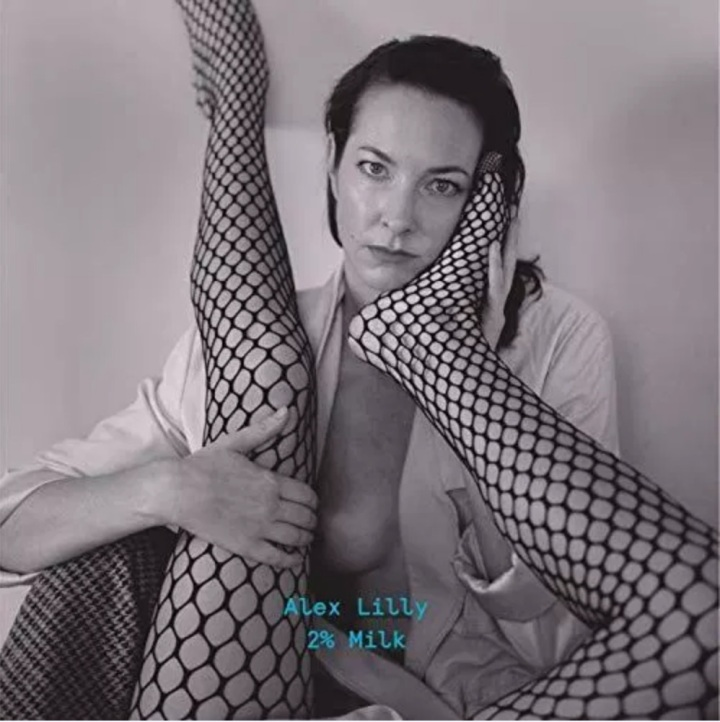 The album cover is a grayscale photo of a caucasian woman with short, dark hair wearing an unbuttoned white blouse. The same woman is holding up a pair of legs wearing fishnet hosiery as one leg extends over her shoulder and the other leg bends at the knee with its foot caressing her face.