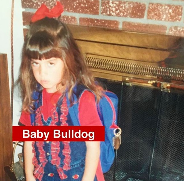 The album cover is an old photo of a young, frowning girl wearing a blue and red outfit, a red bow and her backpack. She is standing in front of a fireplace.