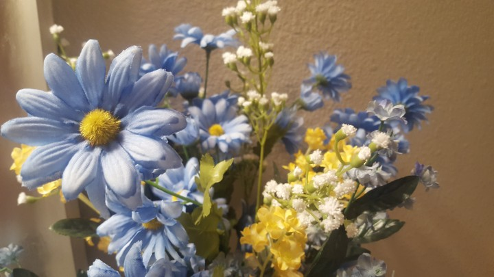 Bouquet with a mixed arrangement of blue, yellow and white flowers is sitting on a bathroom counter for decoration