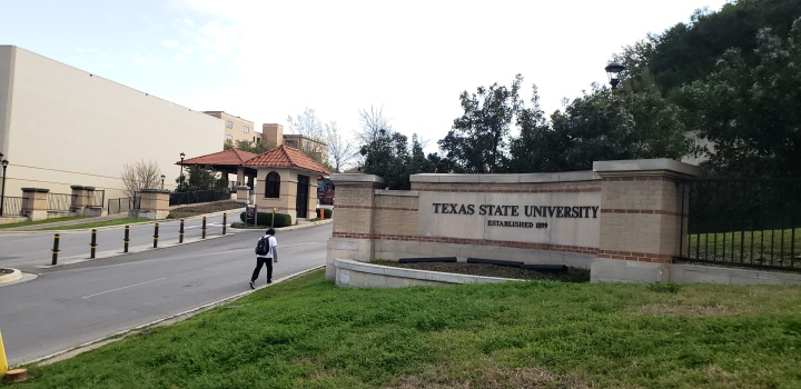 A student walks up into campus by a Texas State sign.