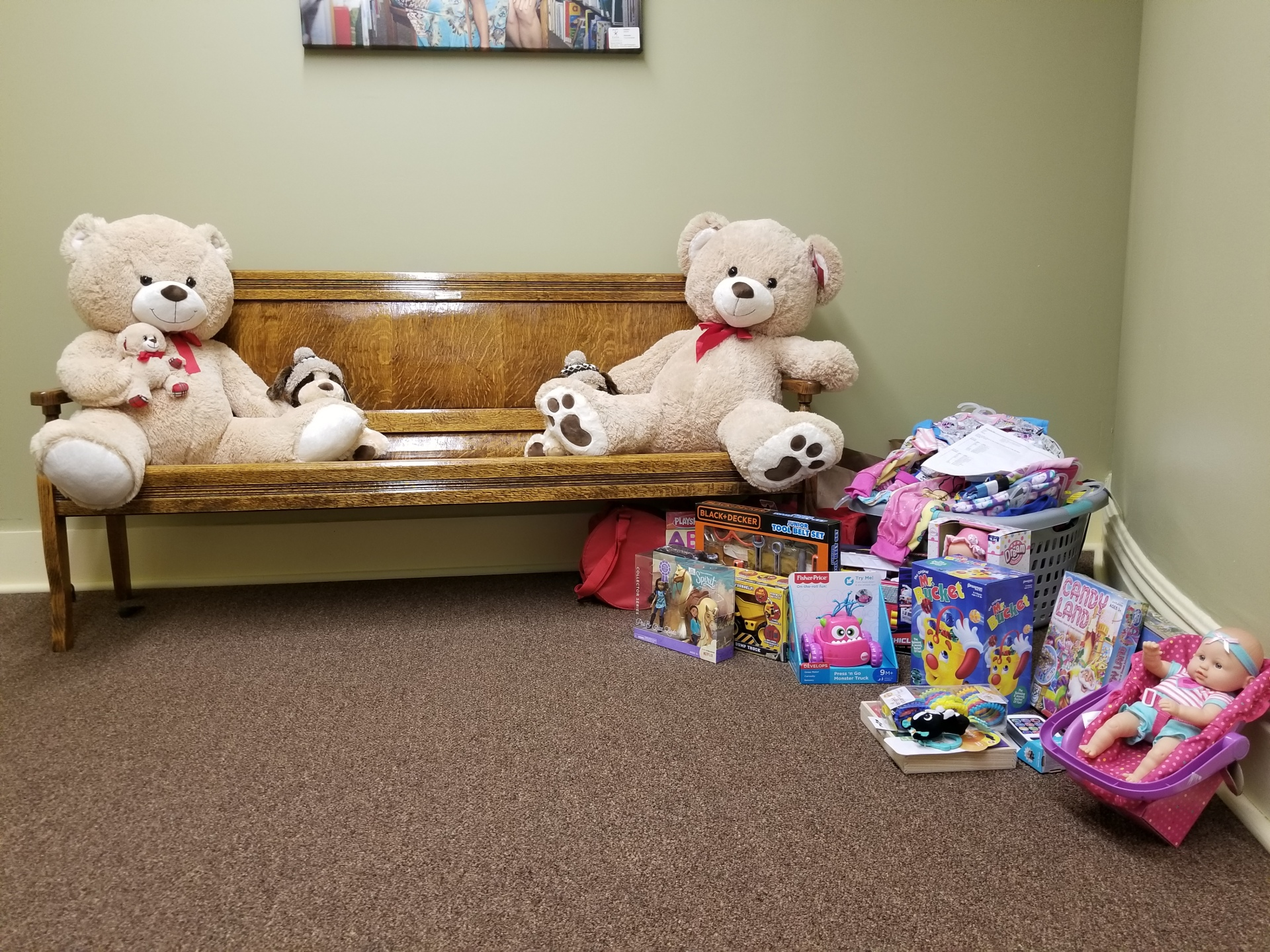 Two teddy bears sit opposite one another on a bench, to the right of the bench on the floor there is a pile of miscellaneous toys, and above the two bears a portrait can be barely be seen in the frame.