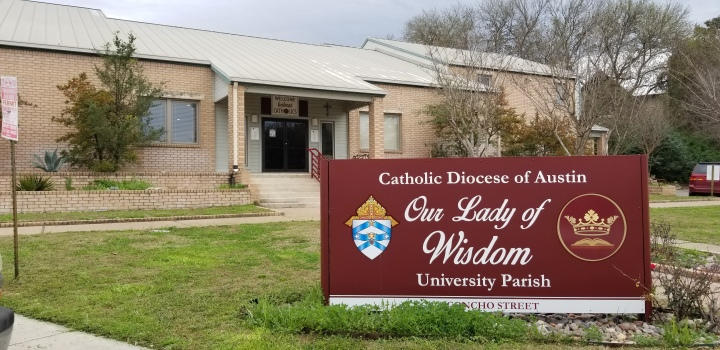 Front side of a church, with a sign that reads Catholic Diocese of Austin Our Lady of Wisdom University parish.