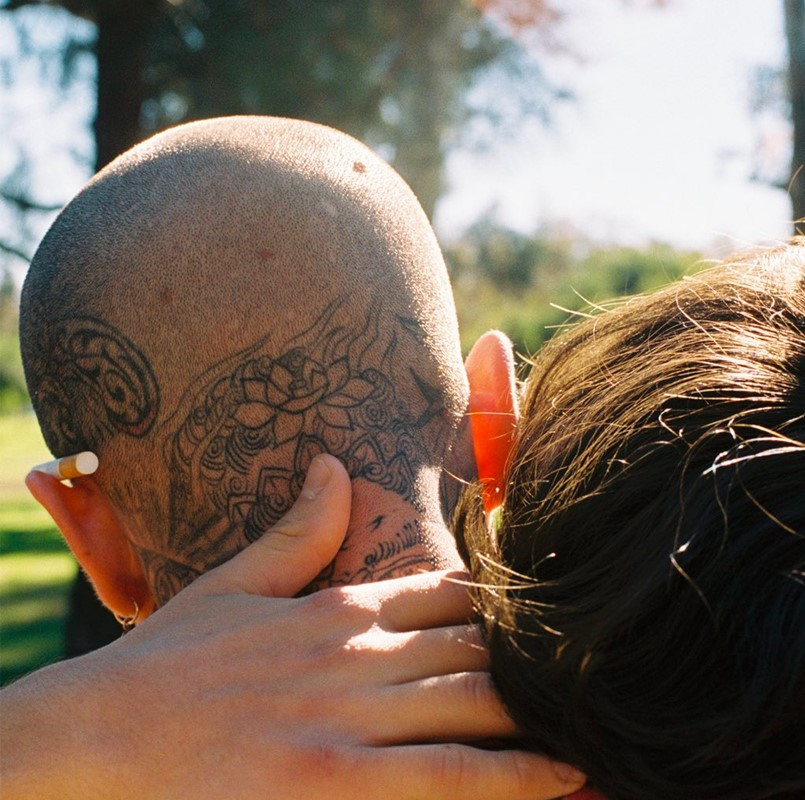 A brown-haired woman rests her head on the shoulder and wraps her hand around the neck of a bald man with head tattoos