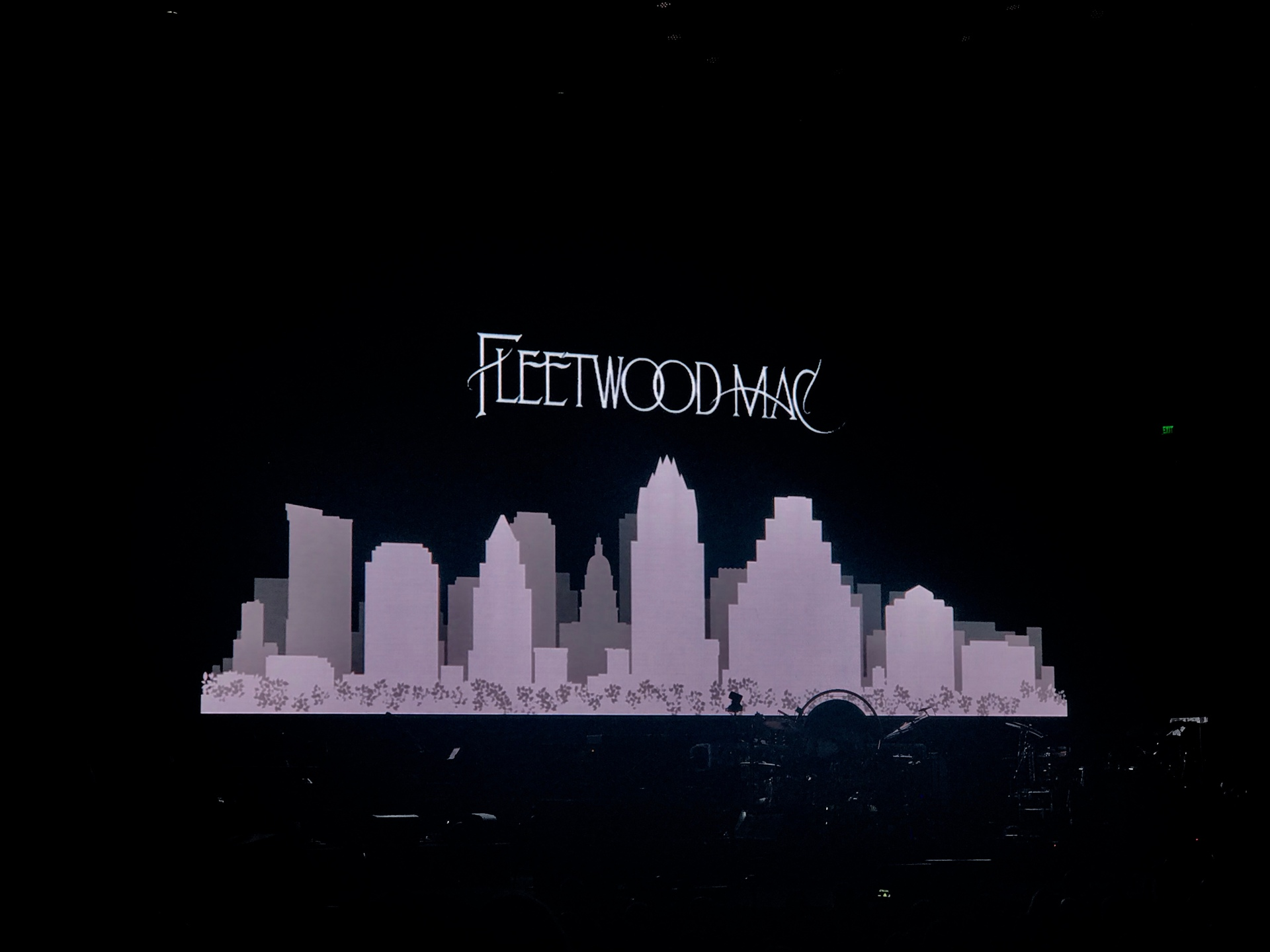 Black screen with Fleetwood Mac written in white and a white city skyline underneath.