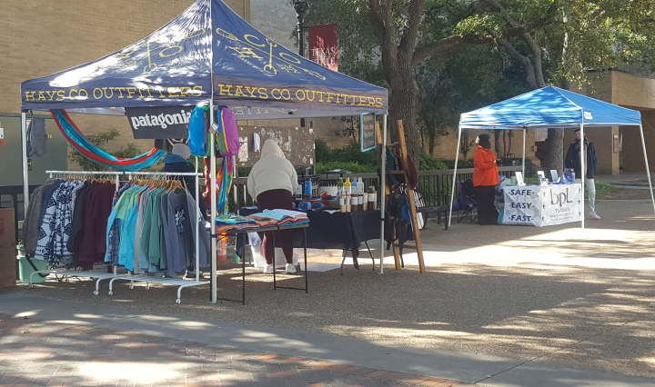 A clothing store named Hays County Outfitters has a pop-up tent with multicolored long sleeve T- shirts, fluffy jackets, and hammocks for sale.