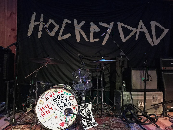 "A banner with ""Hockey Dad"" on it and a drum kit decorated with stickers spelling the band names."