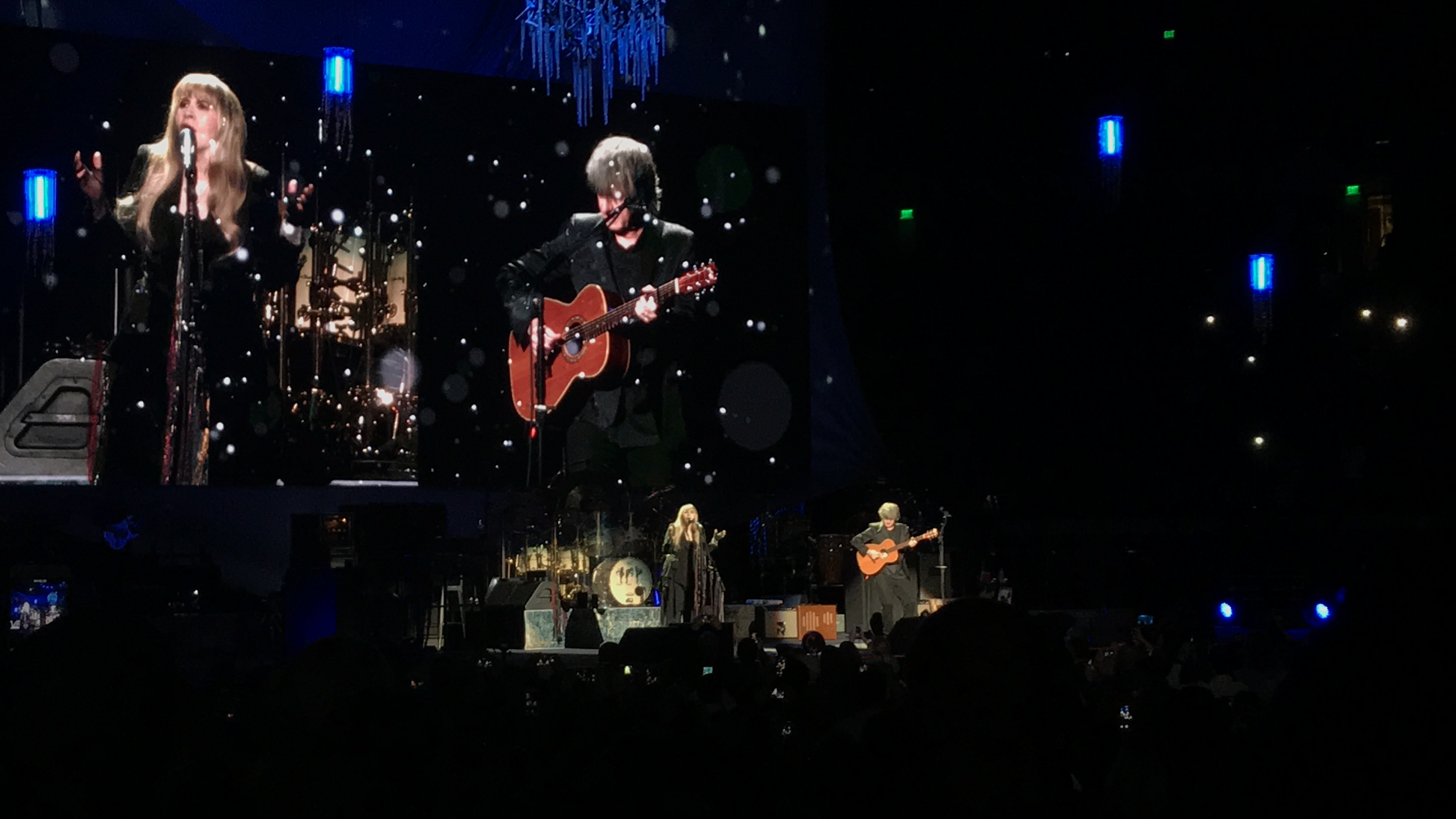 Stevie Nicks sings with her arms raised while Neil Finn is to the right playing guitar.