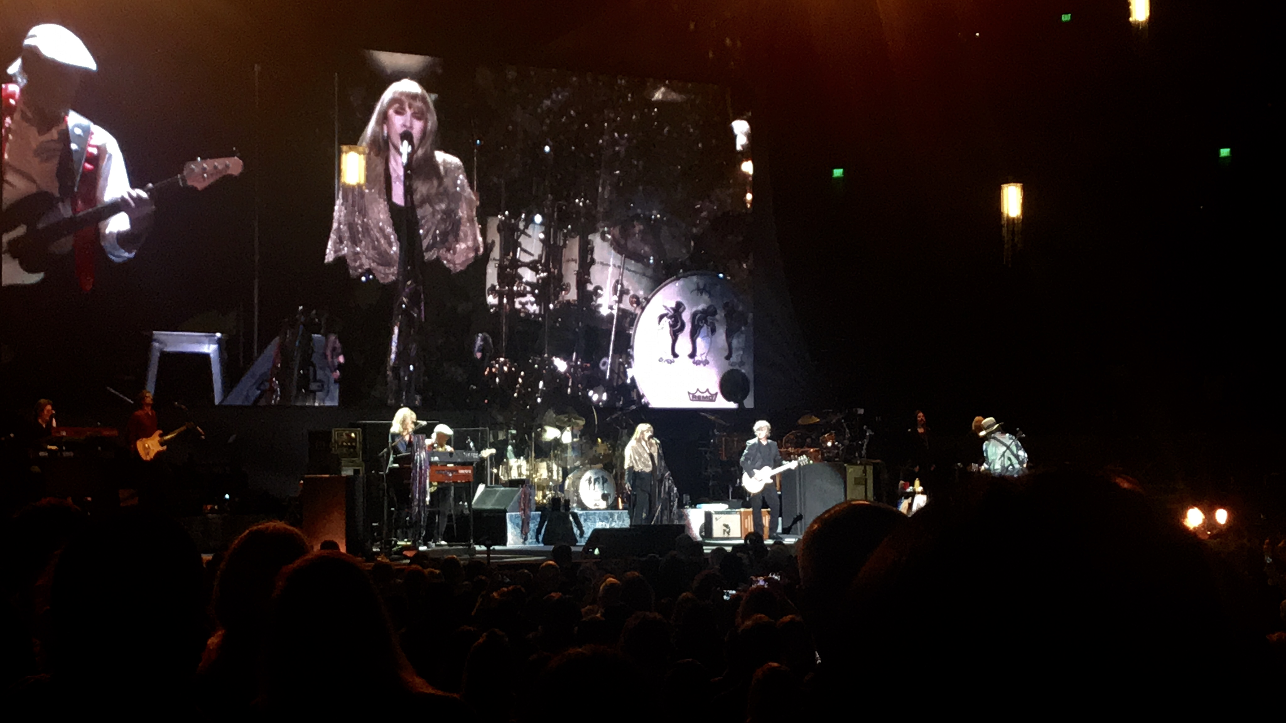 Stevie Nicks sings in the middle wearing a glittery gold shawl. Christine McVie and John McVie are to her left playing keyboard and bass, and Neil Finn and Mike Campbell her to her right playing guitar.