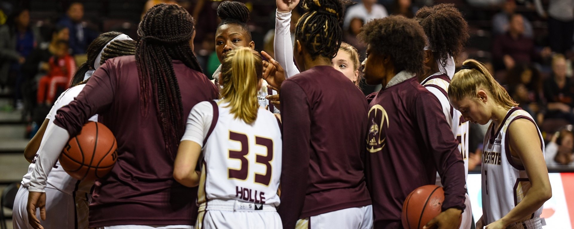 The Texas State women's basketball team in a huddle with one fist raised in the air.