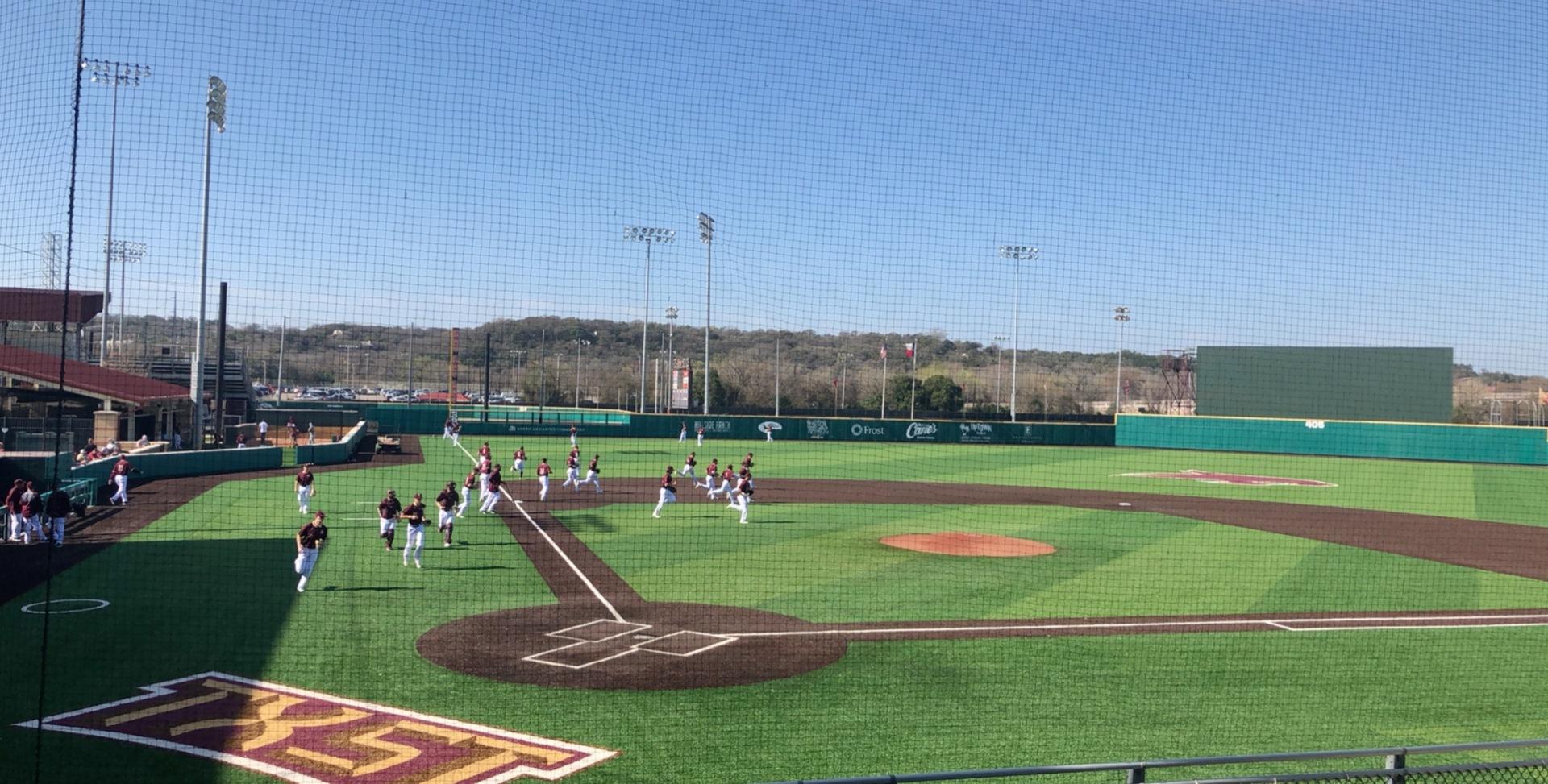 Texas State baseball players jog out on a baseball field.