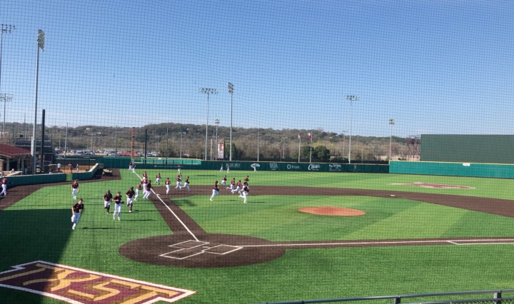 Texas State baseball players jog out on a baseball field.