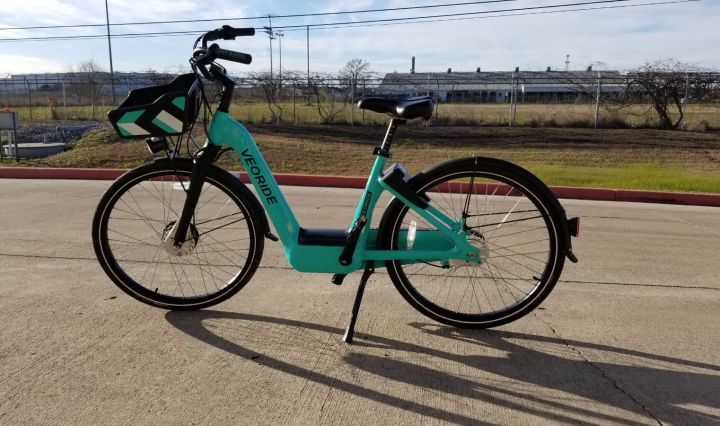Teal-colored Veoride bikes stands with its kickstand out on a side walk