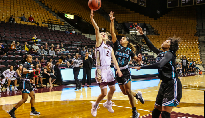Toshua Leavitt drives for a layup on Coastal Carolina's #14.