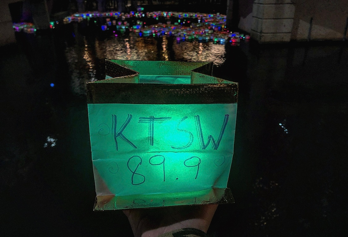A lantern that say KTSW 89.9 with hundreds of other lit lanterns in the background.