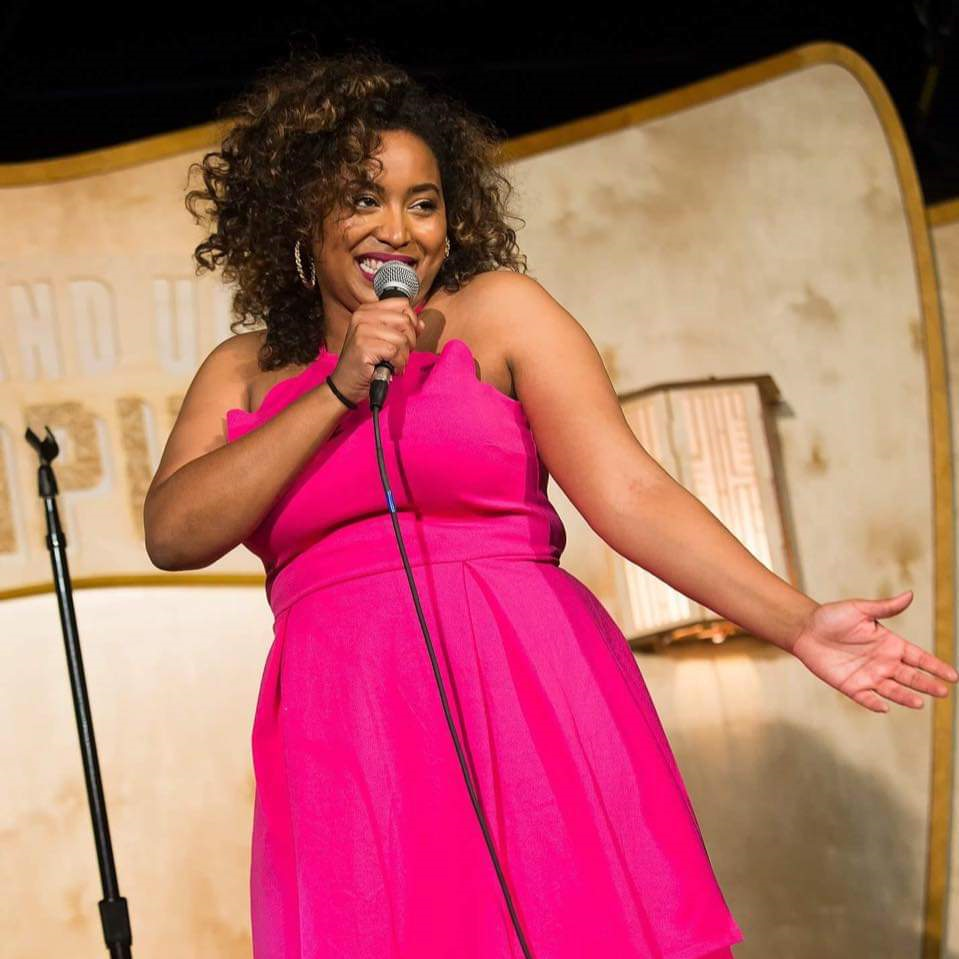 A woman in a pink dress standing on a stage with a microphone.