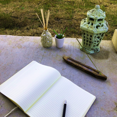 An open journal surrounded by incense, plants, and a lantern.