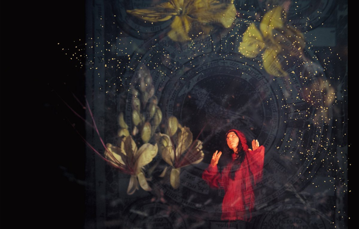 A woman in a red hoodie is surrounded by large yellow flowers sprinkling dust above her on a dark background.
