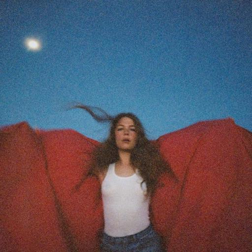 Maggie Rogers holding a red blanket behind her.