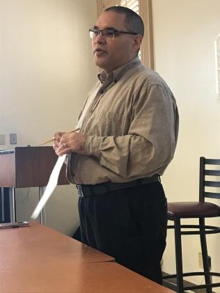 Man presenting in classroom setting.