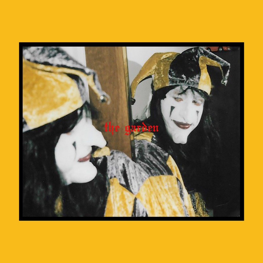 The album cover is one of the twins in a yellow jester costume with face paint looking into the mirror