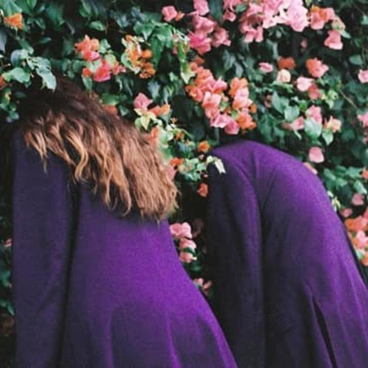 Two people in purple coats with their heads in a bush with pink flowers.