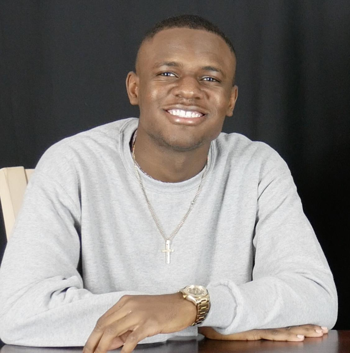 A smiling young man in a gray sweater with a gold watch and a cross necklace.
