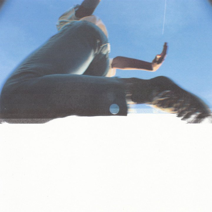 The album cover is a blurry image of someone wearing blue jeans jumping over the camera.