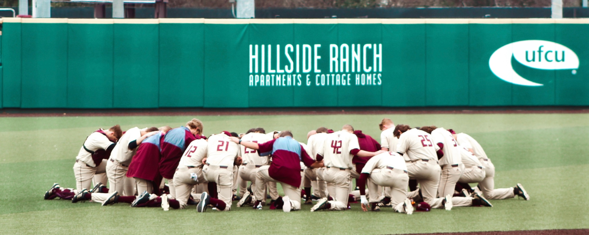 Texas State baseball team huddled up praying in a circle