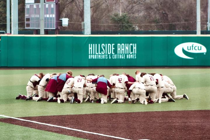 Texas State baseball team huddled up praying in a circle