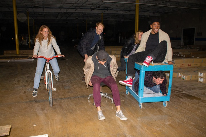 Members of the Ooey Gooeys on multiple different objects including a roller chair and a bicycle riding through the Adamson Bros Woodshop Warehouse.