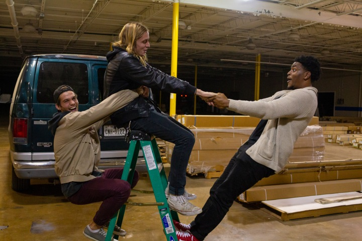 Three members of the Ooey Gooeys balancing each other on a green ladder by holding onto each other.