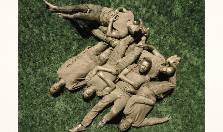 Muddy men laying in green grass