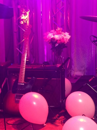 Flowers, balloons, and pink lights on the stage for Smiile's show.