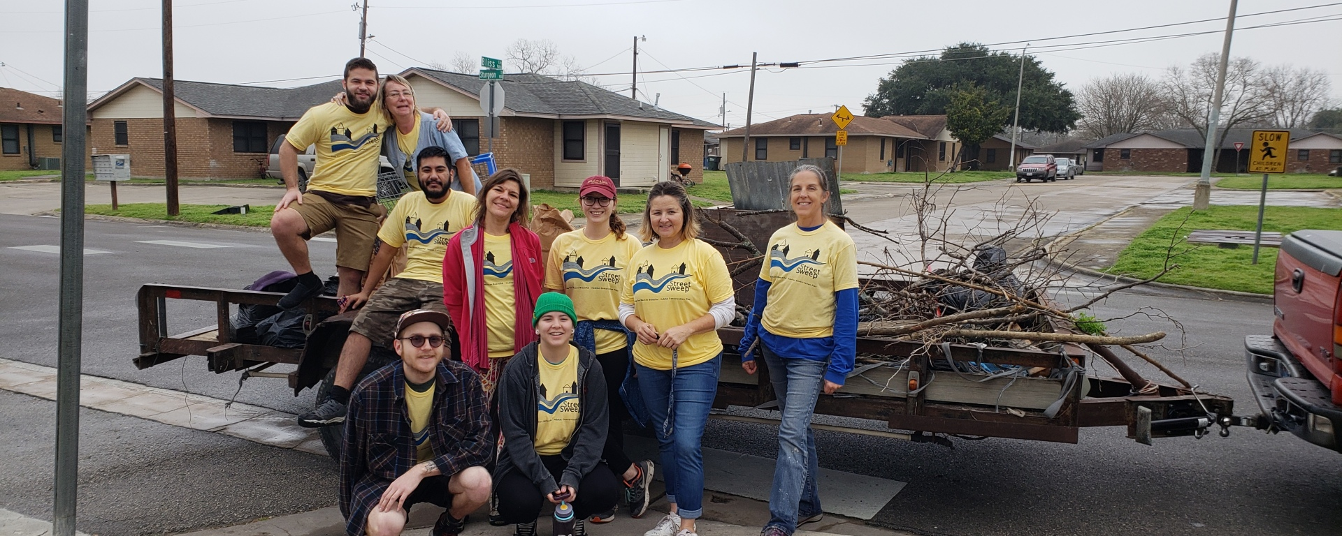 The volunteers are posing next to a pile of trash on a trailer.