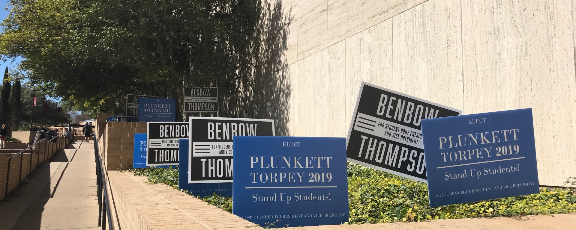 Campaign signs posted with candidates' names on them in landscape next to walkway ramp.