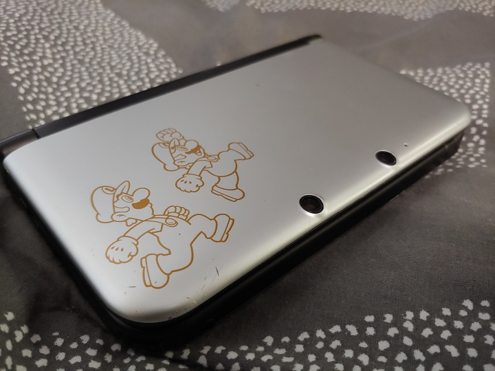 A silver 3DS with decal stickers of Mario and Luigi.
