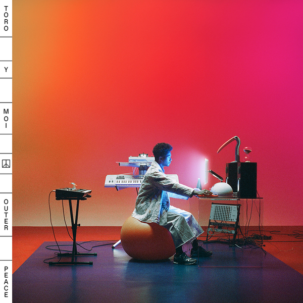 The album cover is of a man sitting on a yoga ball in front of a futuristic computer with a neon pink background.