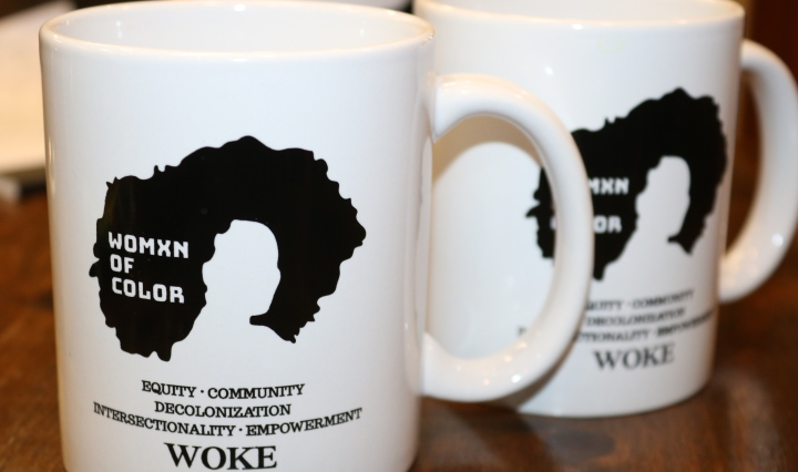 A white mug that shows a black outline of a woman's afro. Beneath the outline are the words , Equity, Community, Decolonization, intersectionality, Empowerment and woke in all Caps.