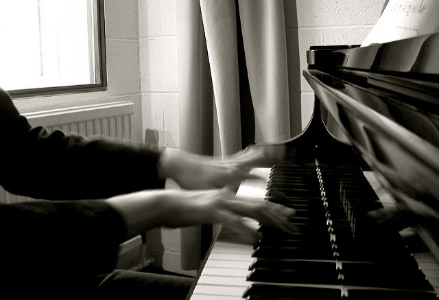 The picture is back and white of two hands playing the piano.