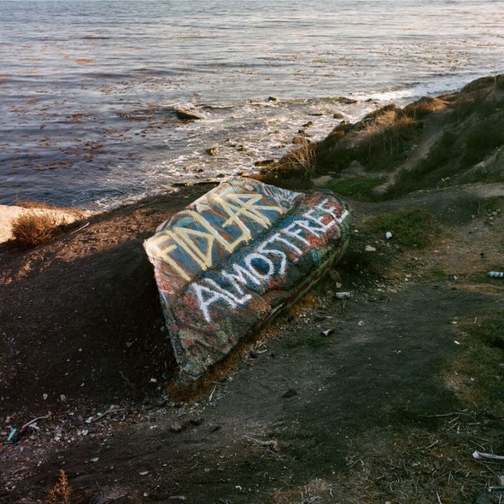 The album cover is a picture of a piece of driftwood next to the shore covered in spray paint, FIDLAR Almost Free is written in yellow and white spray paint on it.