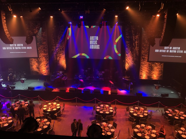 "A dark venue lit with orange, pink, purple and blue spotlight hues. There is one giant center stage and a general floor with banquet tables. Three large screens are projected across on the wall. The center screen reads ""Austin Music Awards"" and the two screens on each side read ""City of Austin and Office of Mayor Steve Adler, Sponsor of the Mayor's House Band""."