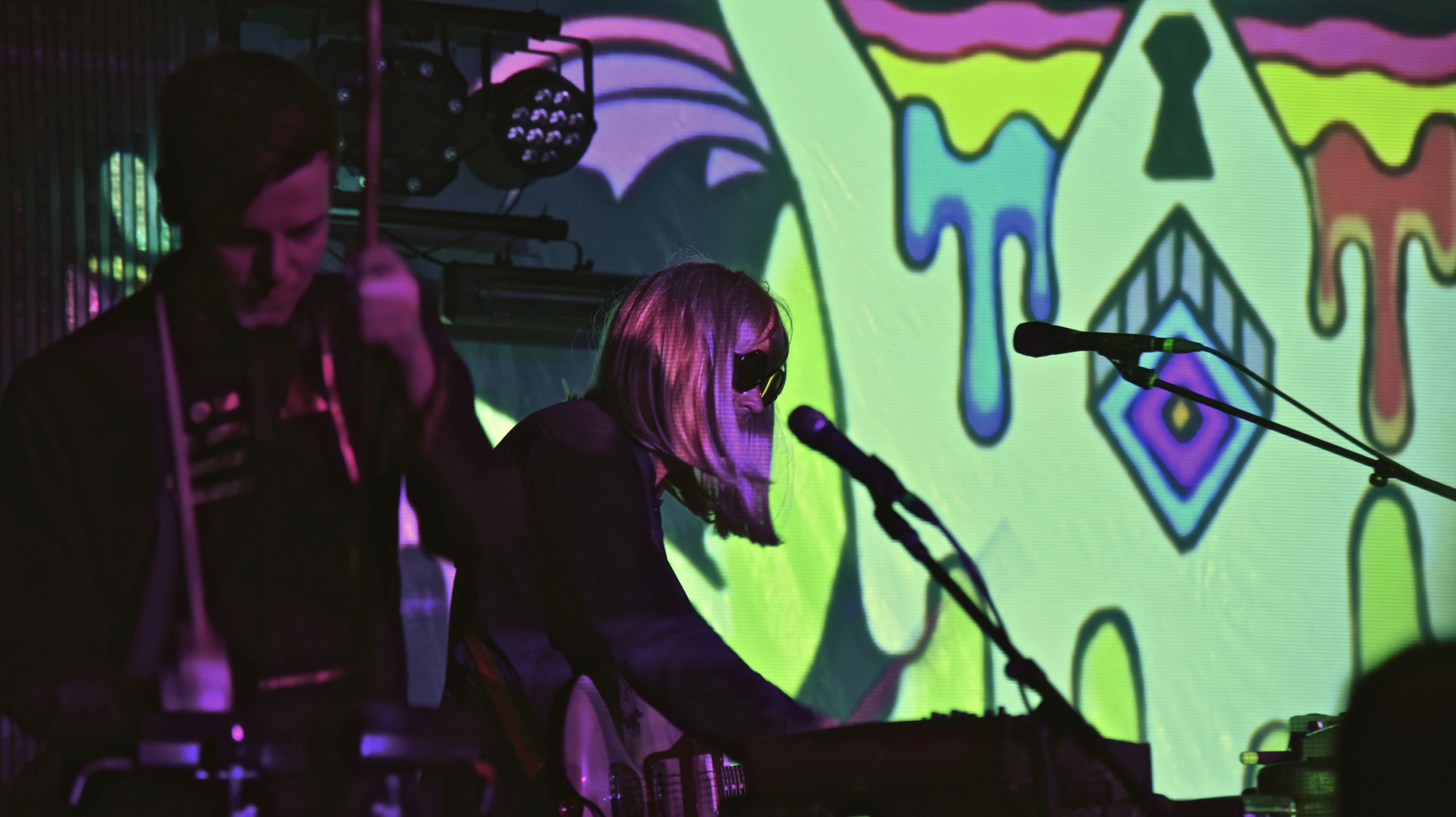 A man drumming next to a man in a blonde wig. There is a colorful background with a dripping slime pattern.