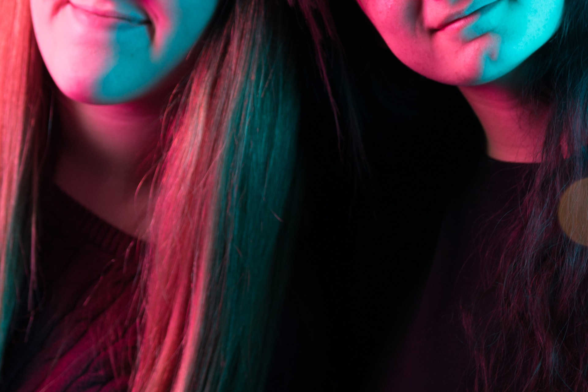 two girls leaning together in pink and blue lighting.
