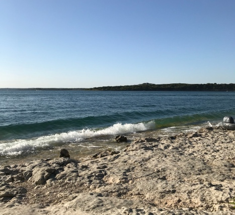 The image features an angled view of Canyon Lake with small waves hitting the rocky shore.