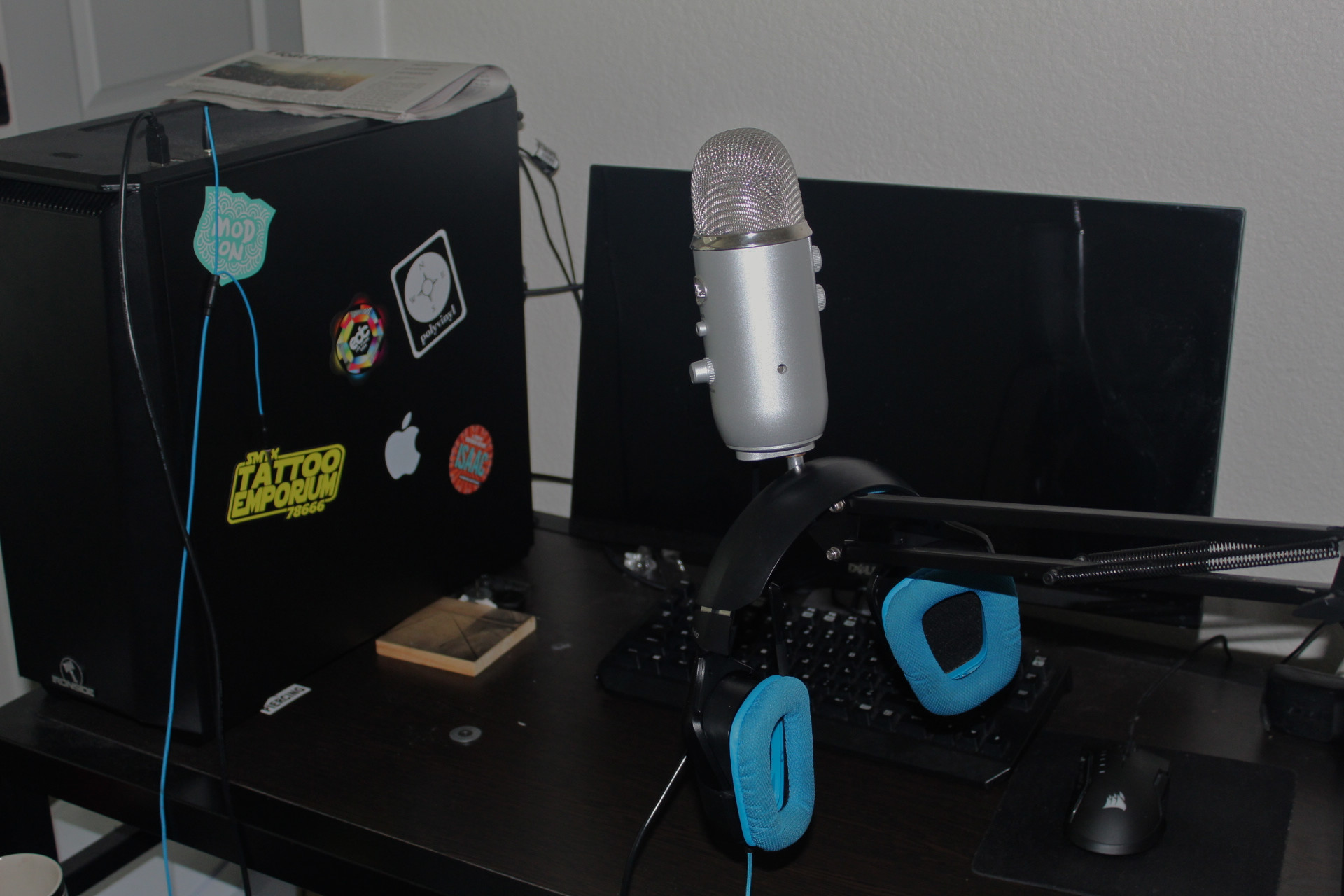 A desk with a computer, microphone and headset on it.