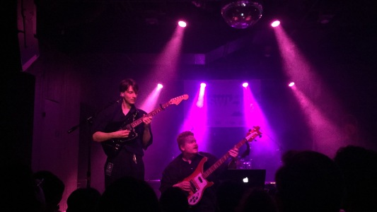 Singer Stephen Fitzpatrick and bassist Auden Laading of Her's performing on a pink stage at The Parish on 6th Street in Austin, Texas during SXSW.