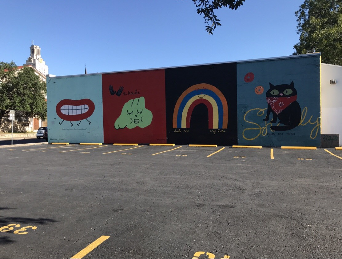 A wall painted with different panels of colorful, simple cartoons.