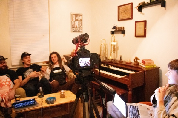 The three members of Kairos (Jake, Jacob, and Brent) sitting on a couch among music instruments and in front of the camera with interviewer, Conner Yarbrough, sitting behind the camera