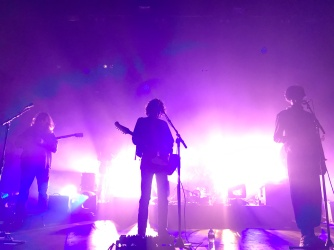The silhouette of the 3 frontmen of Car Seat Headrest play while pink light floods the background