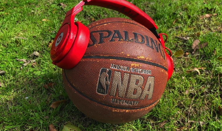 A basketball with a pair of red headphones around it.